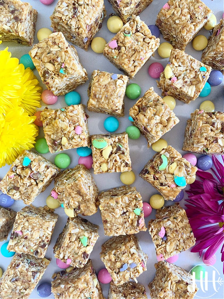 Healthy Easter bliss bites with yellow daisies scattered around and m & m 's.