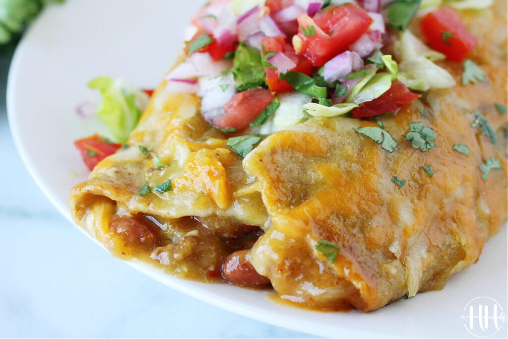 Two cheesy enchiladas on a plate topped with shredded lettuce and pico de gallo.