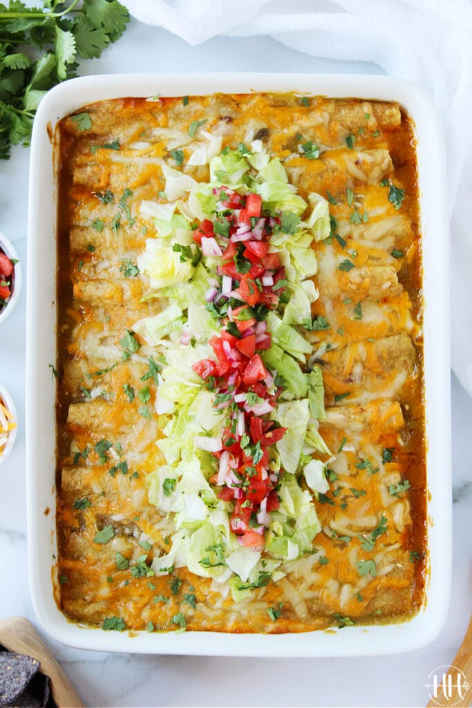 A large pan of enchiladas garnished with toppings.