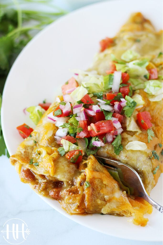 Two cheesy enchiladas ready to be eaten with a fork on a white plate.