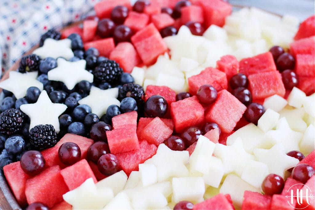 Up close photo of watermelon pieces, white canary melon stars, blueberries, and blackberries in a flag pattern.