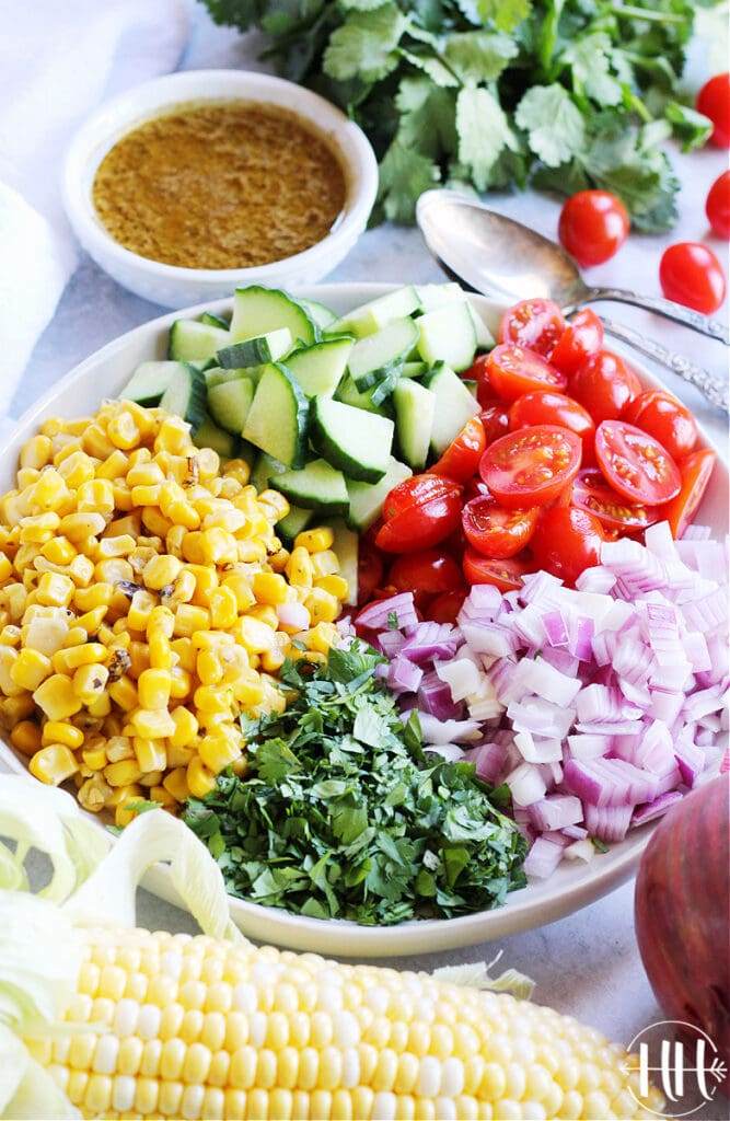 Up close photo of halved cherry tomatoes, quartered English cucumber, diced red onion, minced cilantro, and roasted corn.