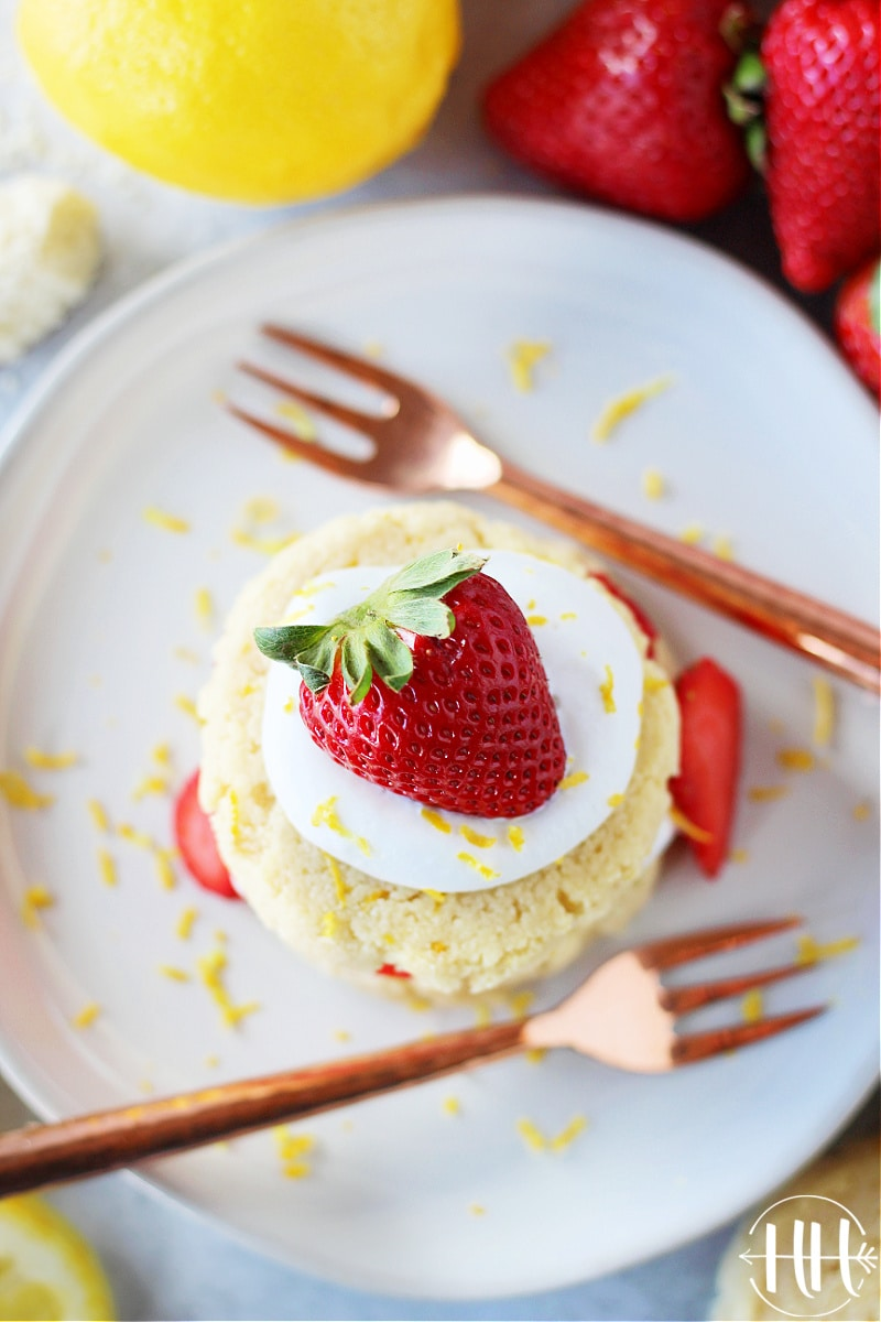 Birds eye view of a white plate, small copper dessert forks and a delicious gluten free berry shortcake.