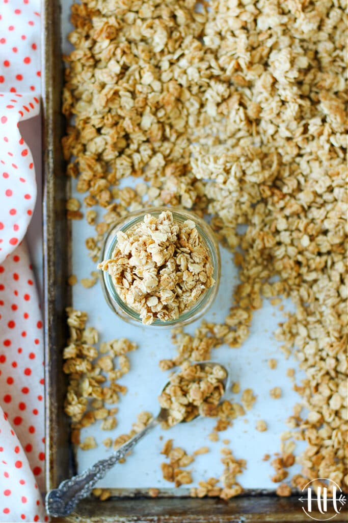 Birds eye view of a mason jar overflowing with French Toast Granola on the sheet pan of the fresh recipe.