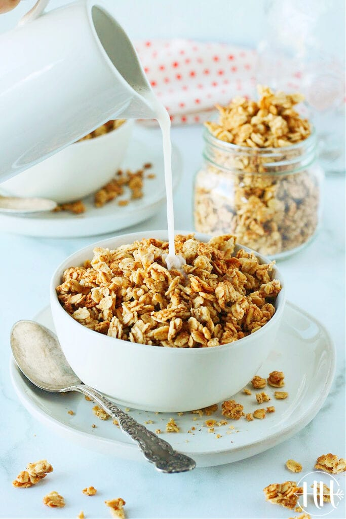 Gorgeous photo of a bowl of French toast granola and small pitcher of almond milk being poured over it.