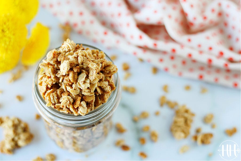 Small mason jar of vegan granola on a white countertop and polka dotted towel and flours.
