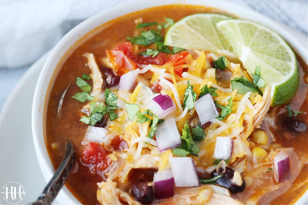 Up close photo of an Instant Pot Chicken Enchilada Soup topped with shredded cheese, cilantro, and red onion.